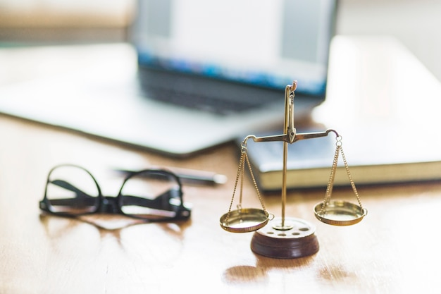 Justice scale and spectacles on wooden desk in courtroom Premium Photo