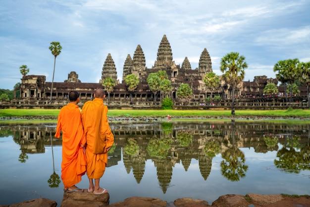 アジアの僧kが立ってシェムリアップのアンコールワットを見て Premium写真