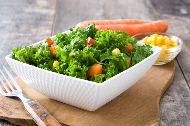Kale salad in bowl with carrot, pepper and sweet corn on wooden table Premium Photo