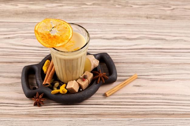 Карак чай или масала чай. популярный индийский напиток в стекле на деревянном столе. Premium Фотографии