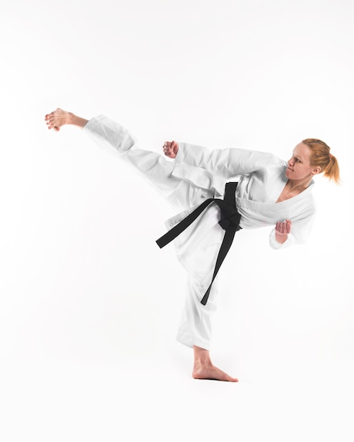 Karate fighter doing side kick Free Photo