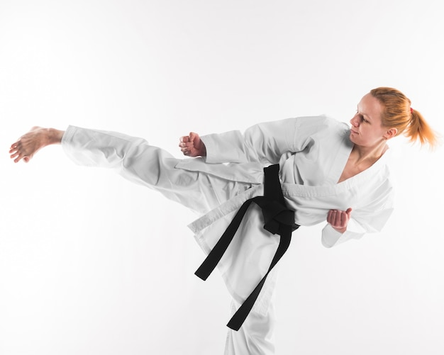 Karate fighter kicking on plain background Free Photo