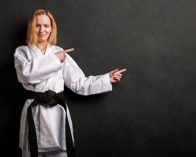 Karate fighter pointing at copy space Free Photo