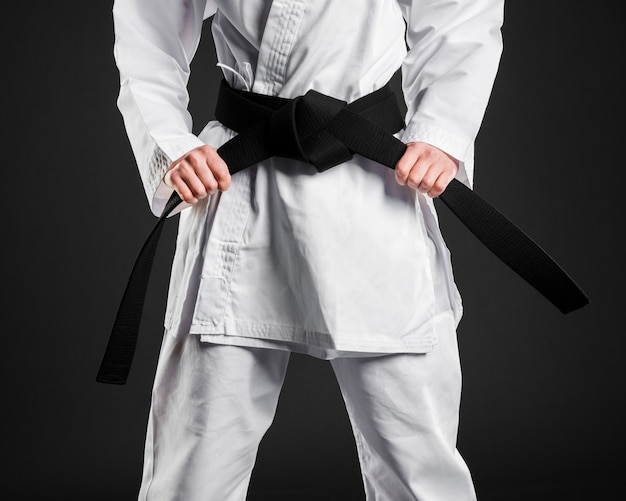 Karate fighter proudly holding black belt Free Photo