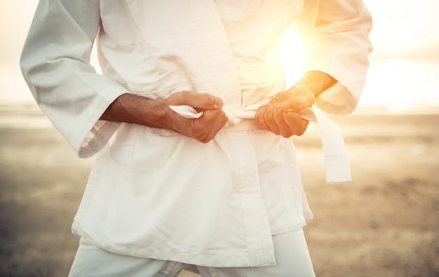 Karate fighter tying his kimono belt up Premium Photo