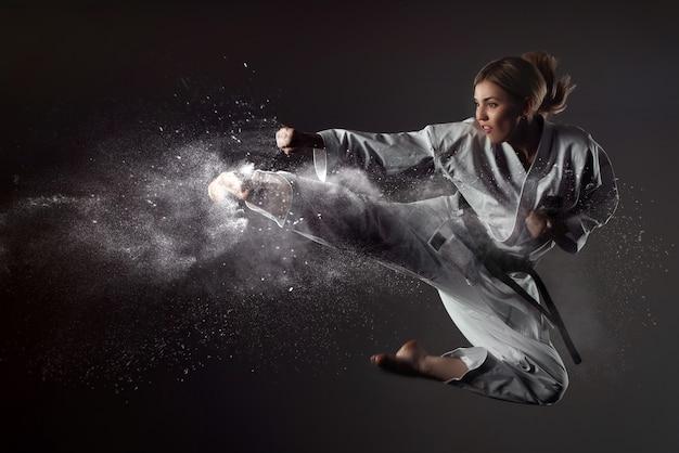 Karate girl bounces and makes a kick Premium Photo