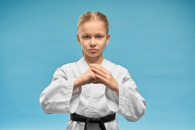 Karate girl with black belt practicing hands position. Free Photo