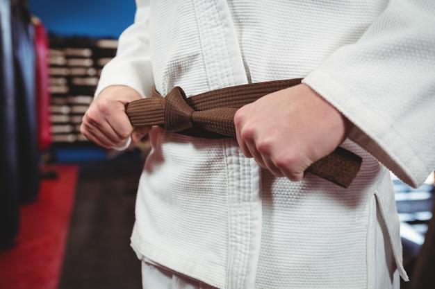 Karate player tying his belt Free Photo