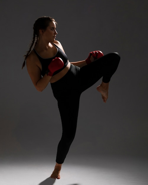 Karate woman giving a kick and dark background Free Photo