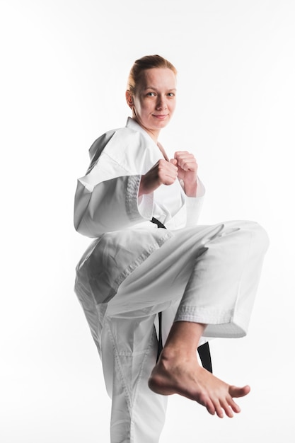 Karate woman kicking front view Free Photo