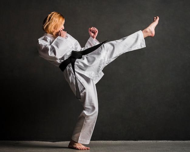 Karate woman kicking full shot Free Photo