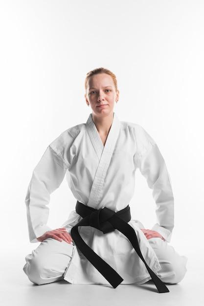 Karate woman sitting front view Free Photo