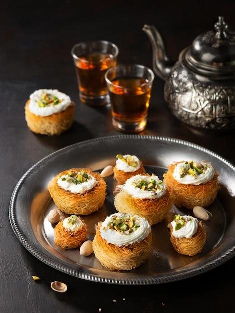 Kataifi、kadayif、kunafa、バクラヴァペストリーは紅茶とピスタチオクッキーを入れ子にします。 Premium写真