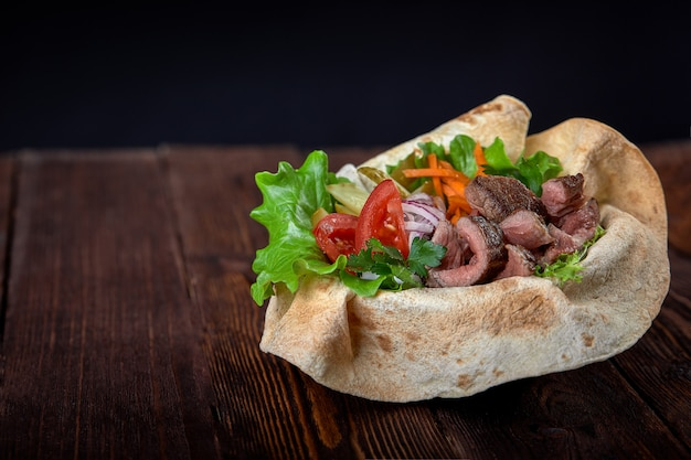 Kebab beef on lavash bread with sauce and vegetables Premium Photo