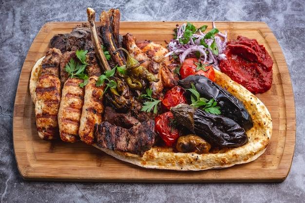 Piatto di kebab con agnello e pollo lula e kebab di tikka verdure grigliate con insalata di cipolle rosse Foto Gratuite
