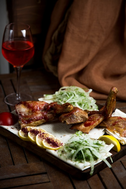 Kebab served with chopped onion, piece of lemon and red wine Free Photo