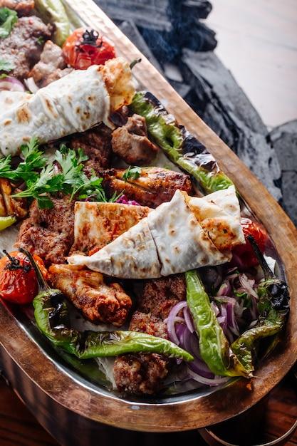 Kebab varieties with vegetables inside wooden platter. Free Photo