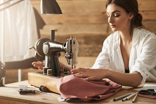 Keep calm and sew with passion. indoor shot of woman working with fabric on sewing machine, trying to concentrate in workshop. young creative designer making new garment for her friend Free Photo