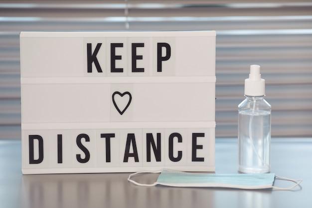 Вывеска keep distance и дезинфицирующее средство для рук на пустом рабочем столе в офисе после пандемии Premium Фотографии