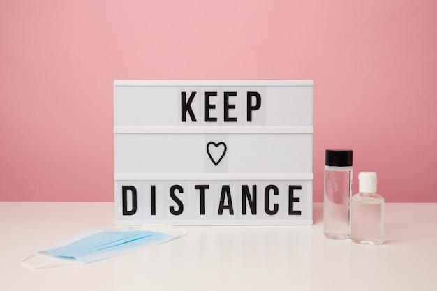 Вывеска keep distance и дезинфицирующее средство для рук на розовом Premium Фотографии