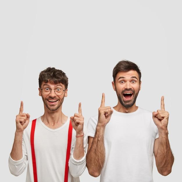 Будьте внимательны! оптимистичные небритые братья указывают обоими указательными пальцами, широко улыбаются, демонстрируя новый баннер, одетые в белые одежды, изолированные над стеной, демонстрируют новый удивительный продукт Бесплатные Фотографии