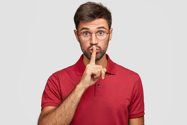 Keep voice down. attractive surprised bearded male makes shush gesture, demnads shut up, wears casual bright red t-shirt, poses against white wall. people, hush, conspiracy, secret concept Free Photo