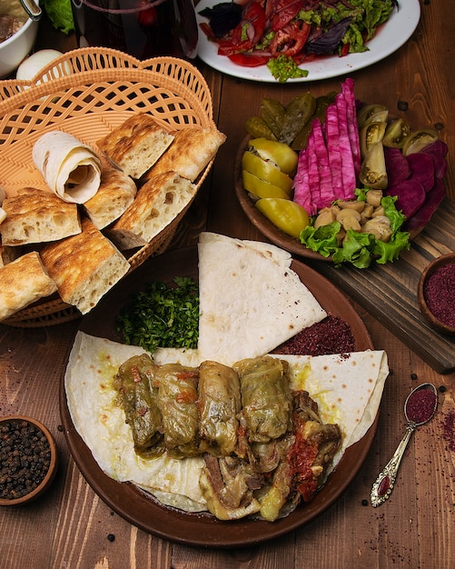 Kelem dolmasi, cabbage leaves stuffed with meat and rice, with beef stew with vegetables in lavash. Free Photo