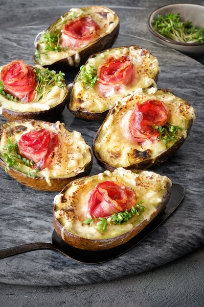 Keto diet dish: avocado boats with crunchy bacon, melted cheese and cress sprouts on dark Premium Photo