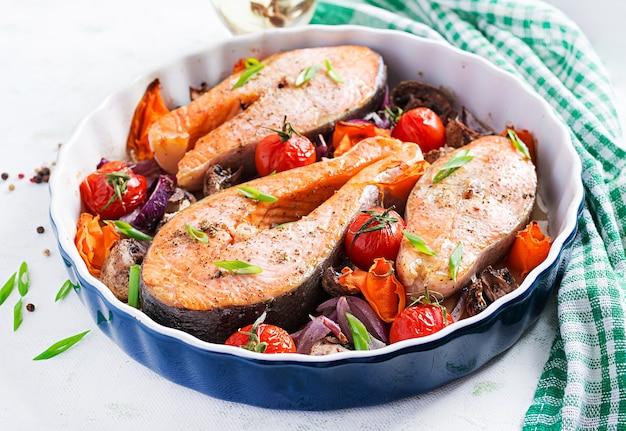 Кетогенный ужин. запеченный стейк из лосося с помидорами, грибами и красным луком. меню кето / палеодиеты. Premium Фотографии