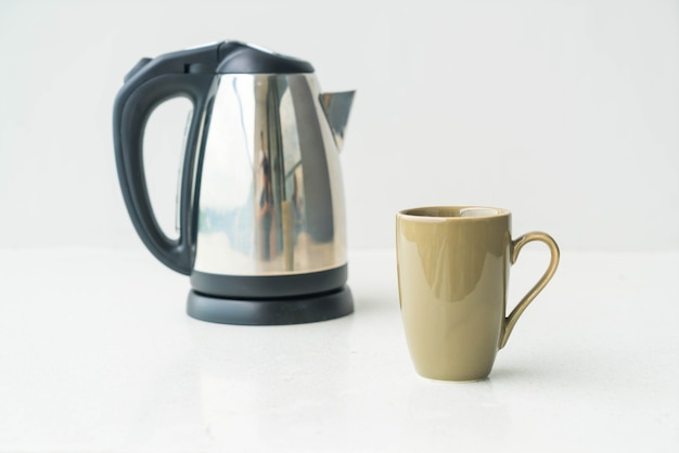 Kettle and cup  on wall background Free Photo