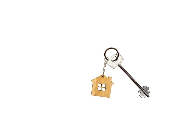 Брелок в форме деревянного дома с ключом на белом фоне, изолировать. строительство, дизайн, проект, переезд в новый дом, ипотека, аренда и покупка недвижимости, бронирование. копировать пространство Premium Фотографии