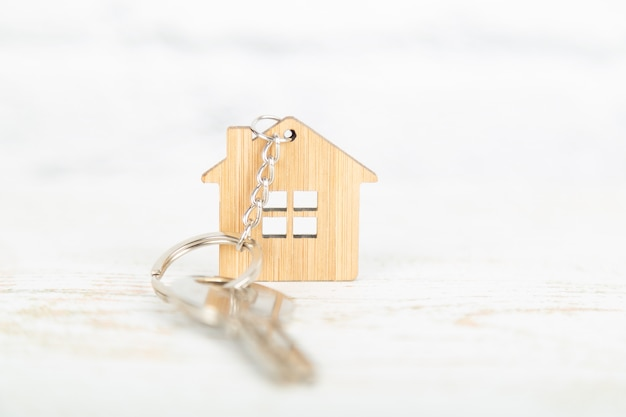 A key on a house shaped wooden keychain Premium Photo