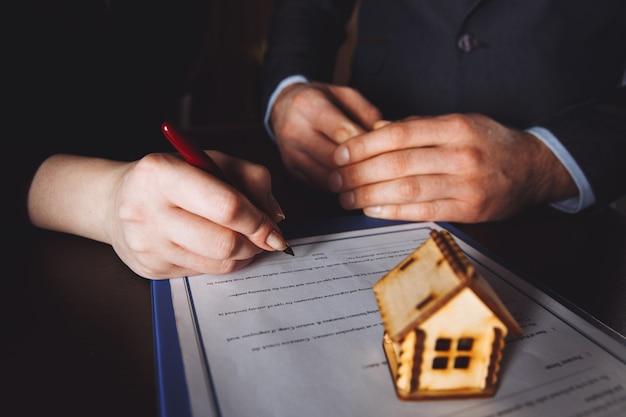 Ключ от дома под рукой у банковского служащего для продажи дома после утверждения ссуды и подписания покупателем контракта в офисе. Premium Фотографии