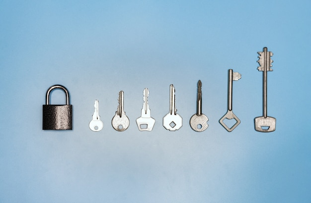Key set concept, lock and different antique and new keys, blue background Premium Photo