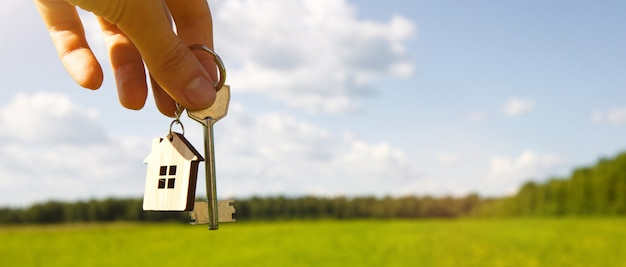 Key and wooden keychain in the shape of a house in the hand in a field Premium Photo