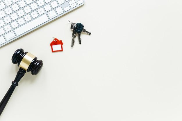 Клавиатура и брелок с деревянным молотком на белом фоне Premium Фотографии