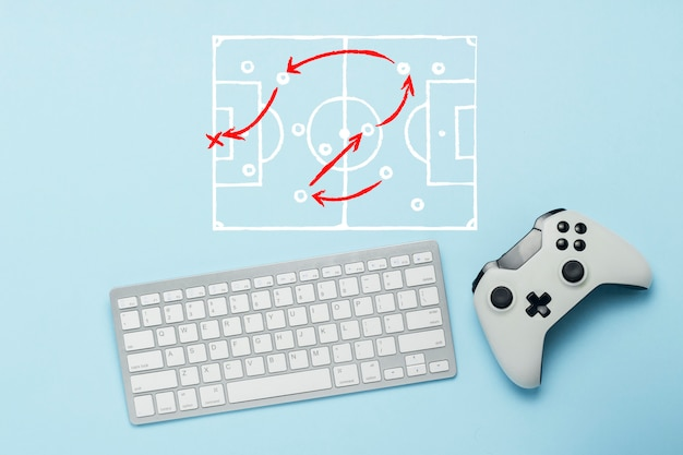 Keyboard and gamepad on a blue background. doodle drawing with tactics of the game. football. the concept of computer games, entertainment, gaming, leisure. flat lay, top view. Premium Photo