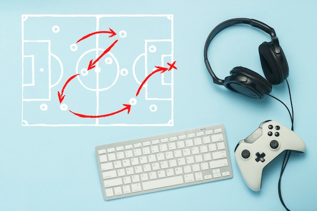 Keyboard, headphones and gamepad on a blue background. added drawing with the tactics of the game. football. the concept of computer games, entertainment, gaming, leisure. flat lay, top view. Premium Photo