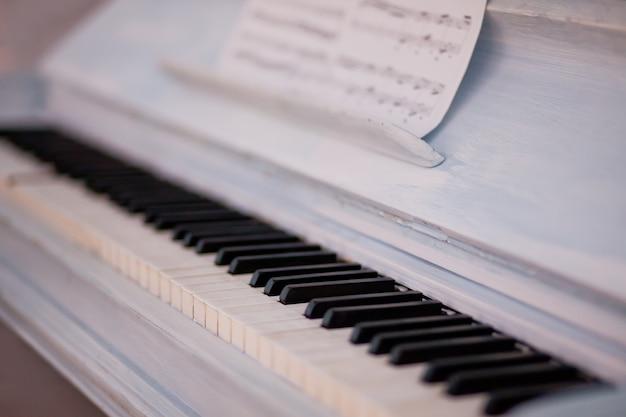 Клавиатура белого винтажного рояля с черно-белым ключом и нотами. Premium Фотографии
