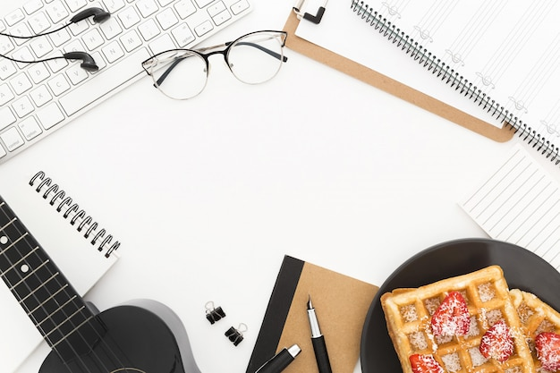 A keyboard, a plate of waffles, glasses, papers and a guitar on a white surface Free Photo