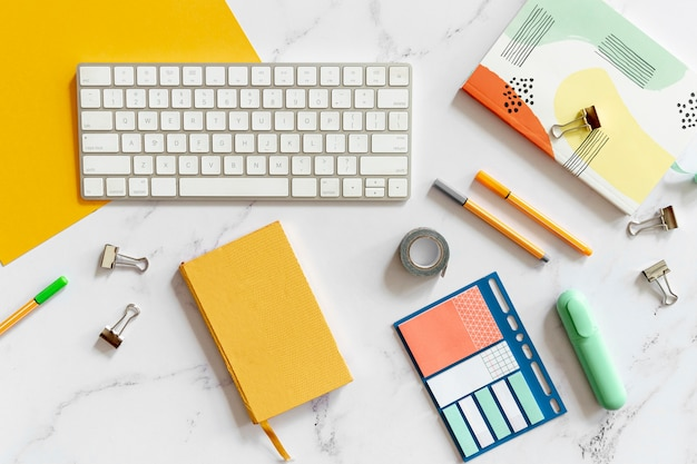 Keyboard surrounded by colorful stationery Free Photo