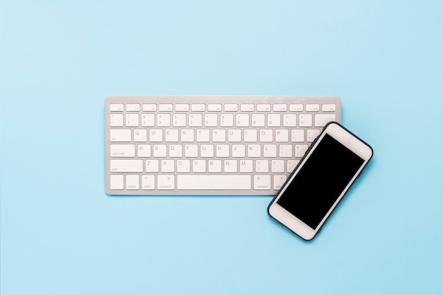 Keyboard and white mobile phone on a blue background. business concept, office work, mobile app and website. flat lay, top view. Premium Photo