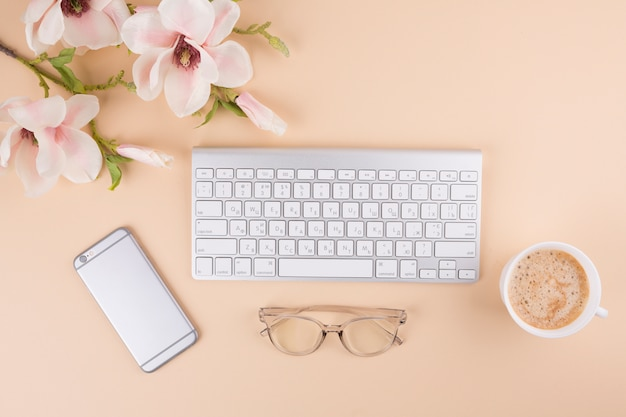 Keyboard with smartphone and flowers on table Free Photo