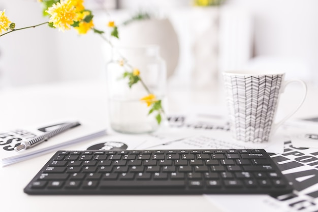 Keyboard with yellow flowers and a cup Free Photo