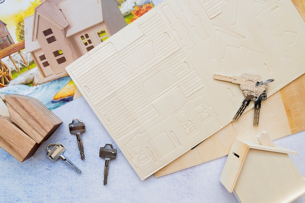 Keys over the card paper house with wooden house model Free Photo