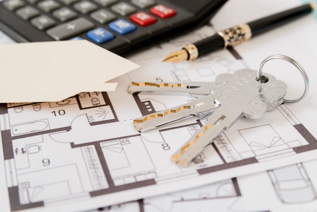 Keys; fountain pen; house paper cut out and calculator on architectural blueprints Free Photo