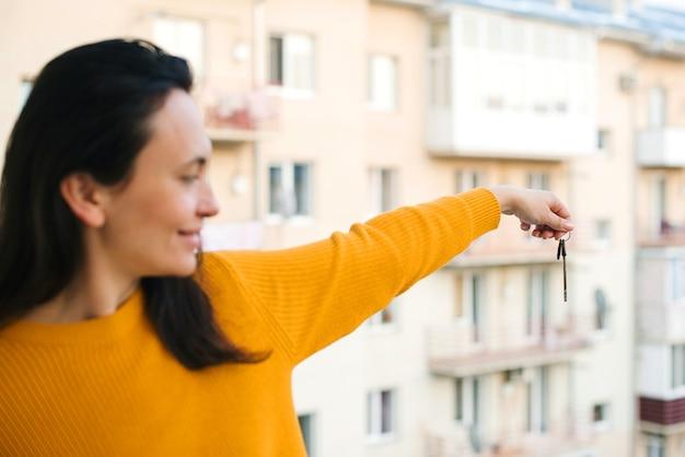 高層ビルに対する新しいアパートからの鍵。新しいアパートの鍵を持っている女性。不動産業界。新しい建物の上に鍵を見せて幸せなアパートの所有者。不動産を買う時間。 Premium写真