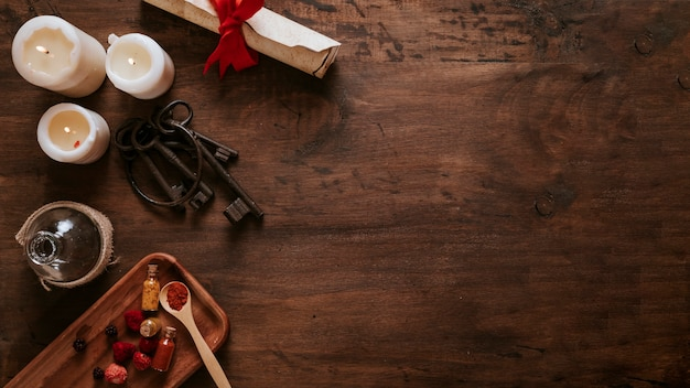 Keys near candles and ingredients on wooden table Free Photo