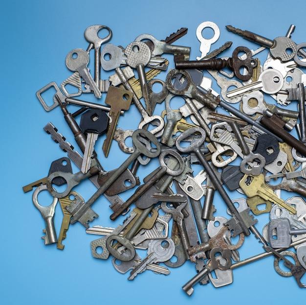 Ключи на синем фоне. ключи от дверных замков и сейфы для сохранности имущества и охраны дома. различные старинные и новые типы ключей. Premium Фотографии