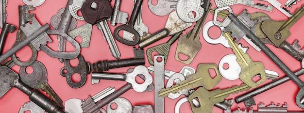 Ключи на розовом фоне. ключи от дверных замков и сейфы для сохранности имущества и охраны дома. различные старинные и новые типы ключей. Premium Фотографии